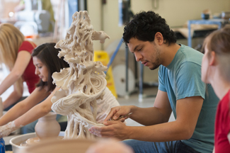 Student working on a large sculpture