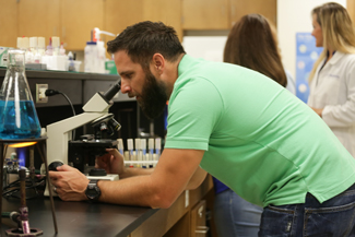 Male student looking through microscope
