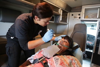 EMT performing exam in ambulance
