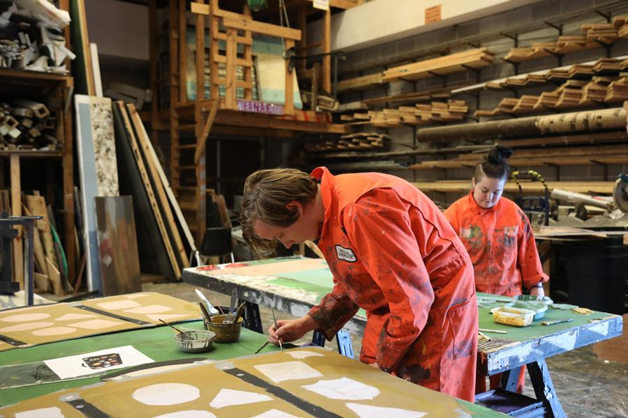 Students hand painting set pieces