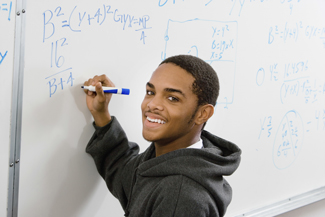 Male student solving math problem on whiteboard